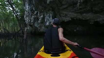 elder man rows kayak along river