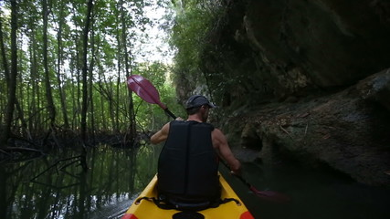 man drifts kayak past cliff and mangrove trees