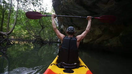 man drifts in kayak and lifts paddle over head