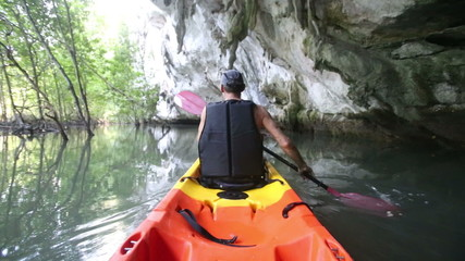 strong elder man rows kayak along river past cliff cave