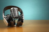 Fototapety Vintage microphone and headphones on green background. Concept a