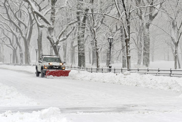 Truck with snowplow clearing road during snowstorm