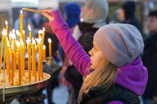 Leinwanddruck Bild Little blond girl with candles in Orthodox Church