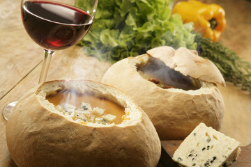 Hot vegetable soup served in bread with a glass of red wine