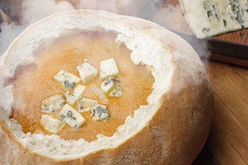 Hot vegetable soup served in bread with cheese
