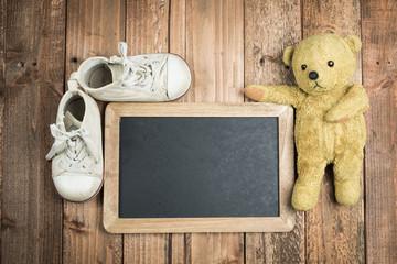 黒板と熊の縫い包みと履き古した子供用の靴