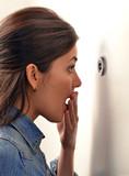 Mujer sorprendida viendo a través de ojo mágico de puerta.
