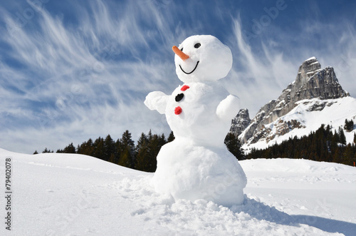 Leinwandbild Motiv Funny snowman against Swiss Alps