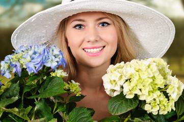 Junge blonde Frau mit Topfblumen
