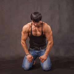 Young bodybuilder is on his knees