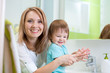 Happy mother and child washing hands with soap in bathroom