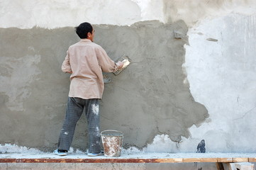 worker plasterer wall aligns with tools