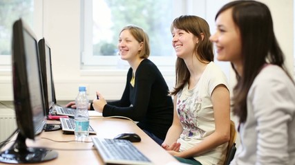 College students sitting in a classroom, using comput