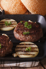grilled burgers with onion and garlic on the grill. vertical