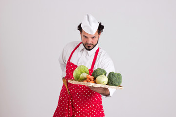 Handsome Headcook is Holding a Wicker Tray with Vegetables