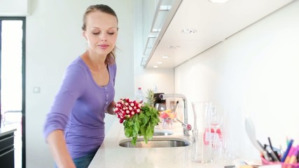 Young woman doing housework, cleaning her modern kitchen