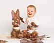 Kleines Baby mit Schokoladen-Osterhase - 79406417