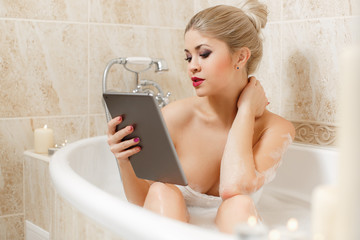 Beautiful woman in a bathtub with a tablet PC.