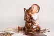 Kleines Baby mit Schokoladen-Osterhase - 79407696