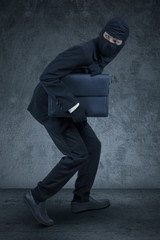 Businessperson with mask stealing a briefcase