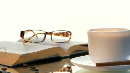 Delicious coffee and book with glasses, cinnamon, beans on white