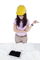 Female construction specialist looking at blueprints