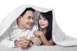 Hispanic couple on bed under blanket