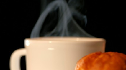 Cup with hot coffee and top of cake on black background