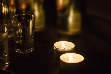 Candles and glass on the old wooden table in the night