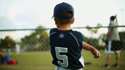 Kid on baseball uniform stretching behind fence by practice
