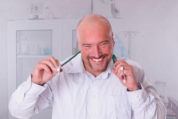 Hausarzt, lächelnd in seiner Praxis
