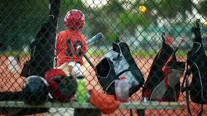 Kid swinging baseball bat. Bags and helmets by fence at field