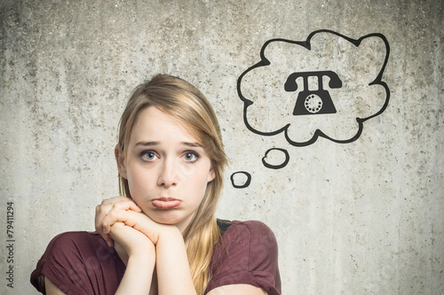Leinwanddruck Bild Junge Frau denkt an Telefon