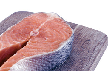 Salmon steak on cutting board isolated on white