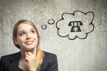 Junge Frau denkt an Telefon