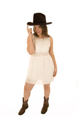 Cowgirl wearing a white dress tipping her cowboy hat