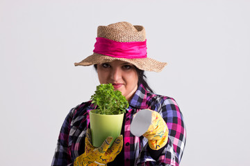Dark Hair Woman in Gardening Outfit is Showing with Scoop Toward