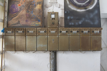 View of old row of electrical boxes on a wall.