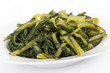 Prepared boiled dandelion greens bowl over white - 79412804
