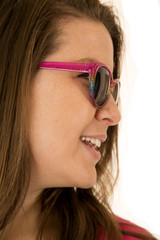 Side portrait of a young woman wearing pink sunglasses