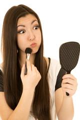 Cute teen model applying makeup making funny face