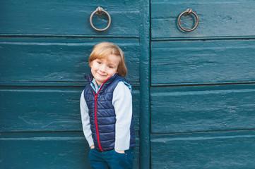 Outdoor portrait of a cute little boy wearing blue waistcoat