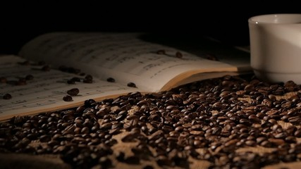 Aromatic coffee beans with music on sacking, black background