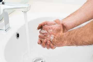 Washing very dirty hands with soap under running water.
