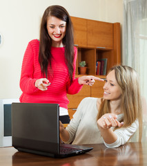 women looking to laptop at table