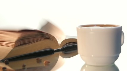 Cup of delicious coffee, milk with turning pages book isolated