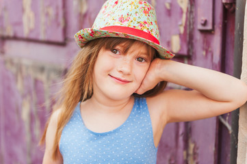 Summer portrait of a cute little girl wearing colorful hat
