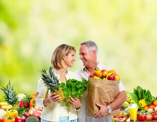 Senior couple with vegetables green background.