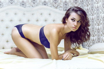 Sexy brunette lying on the bed in underwear.