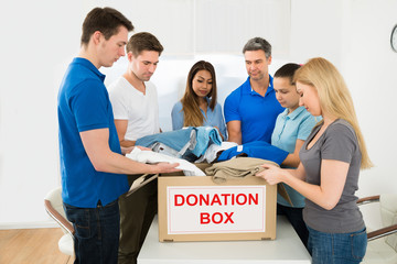 Volunteers Holding Clothes To Donate